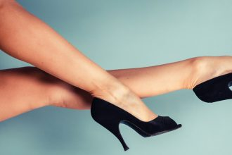 Sexy female legs wearing high heels against a blue background