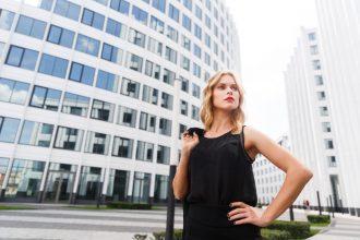 Elegant business woman in black posing near white buildingsrs