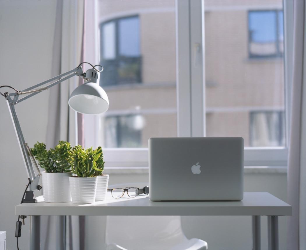 magazynkobiet.pl - silver macbook air and goose neck lamp 939331 1 1050x857 - Podpowiadamy jak wybrać biurko komputerowe